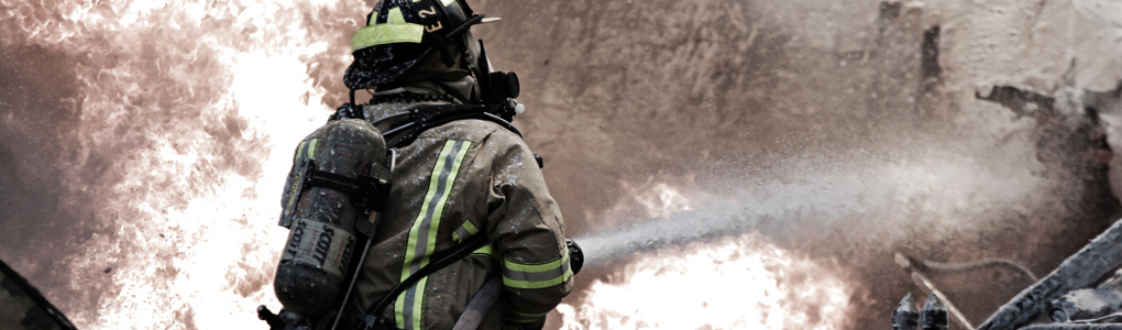 Firefighter in full gear, using firehouse